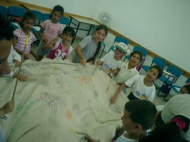 kids drumming on a pow-wow drum in DARIA workshop - ISRAEL