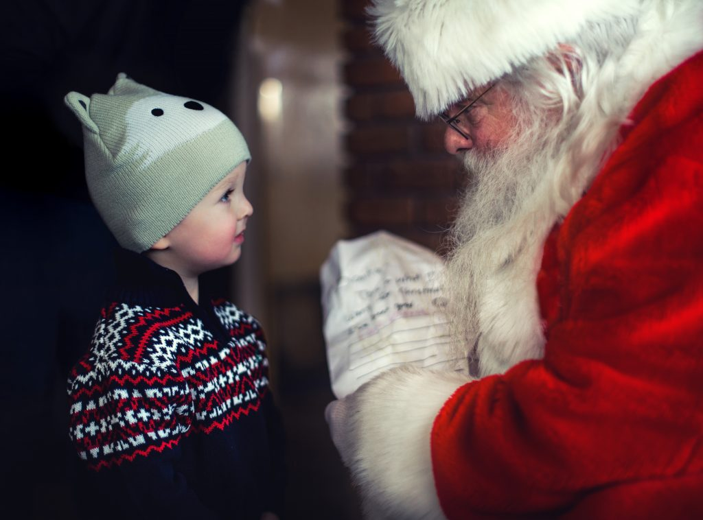 Photo of small child talking to Santa