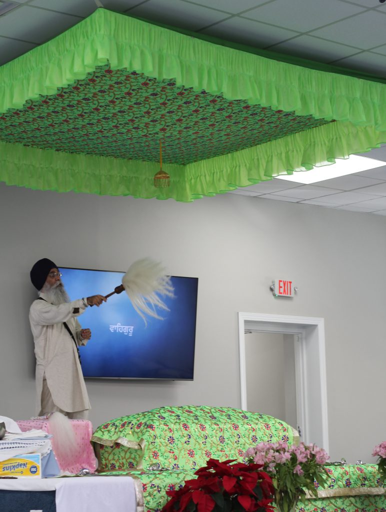 Sikh leader waving chaur over Guru Granth Sahib