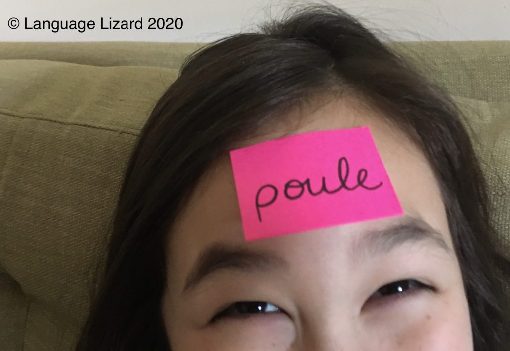 "kid with sticky note that says ""poule"""