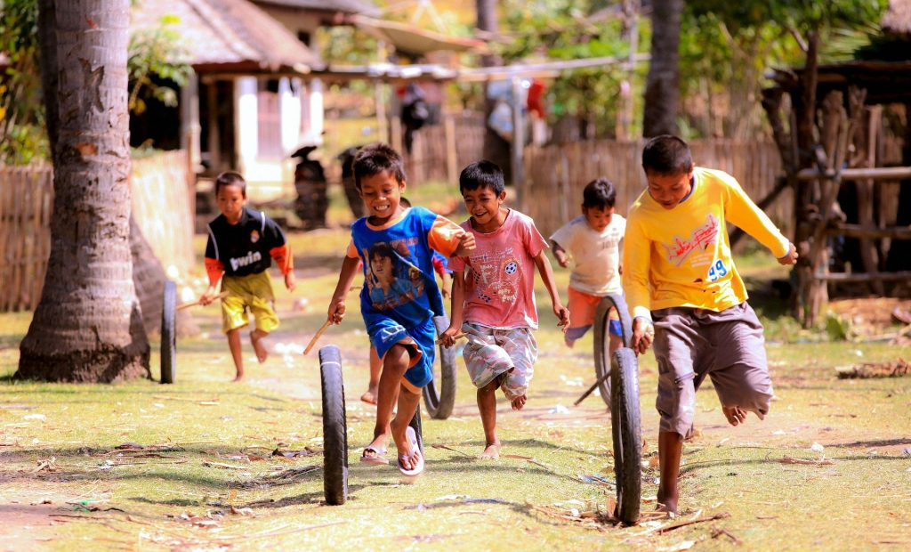 boys running and laughing as they roll tire tubes with sticks - explore cultures