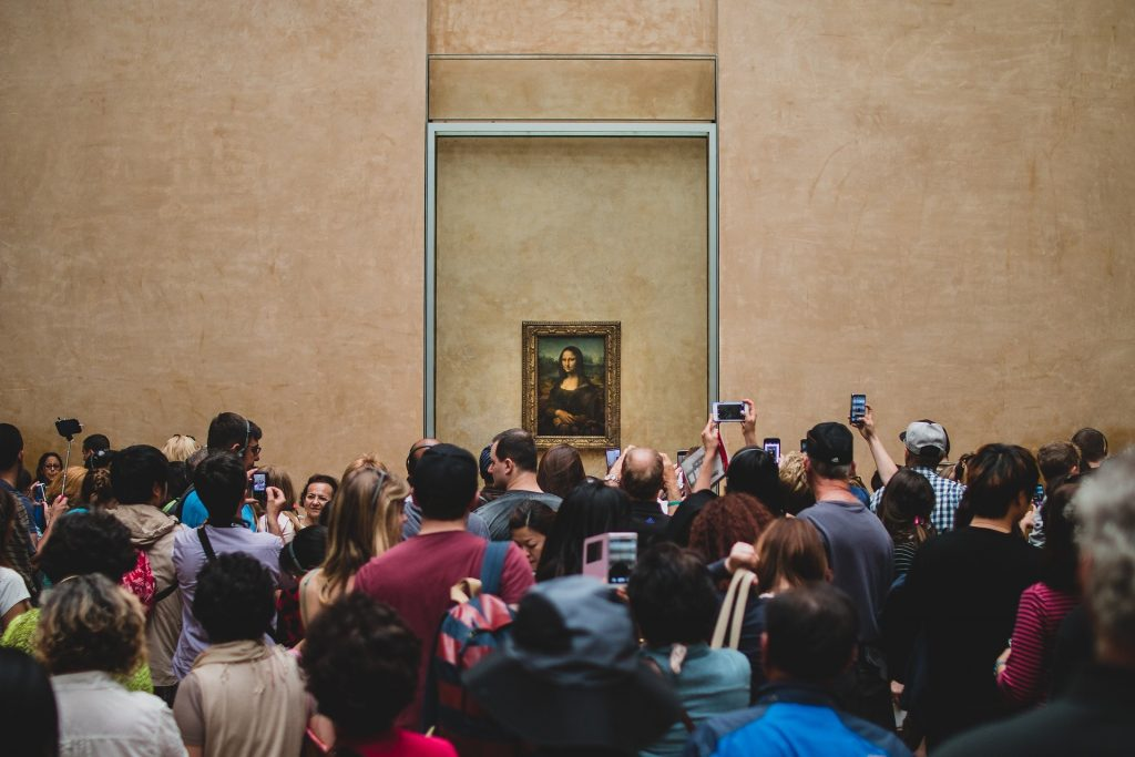 photo of the Mona Lisa, hanging in the Louvre, with the usual crowd gathered around