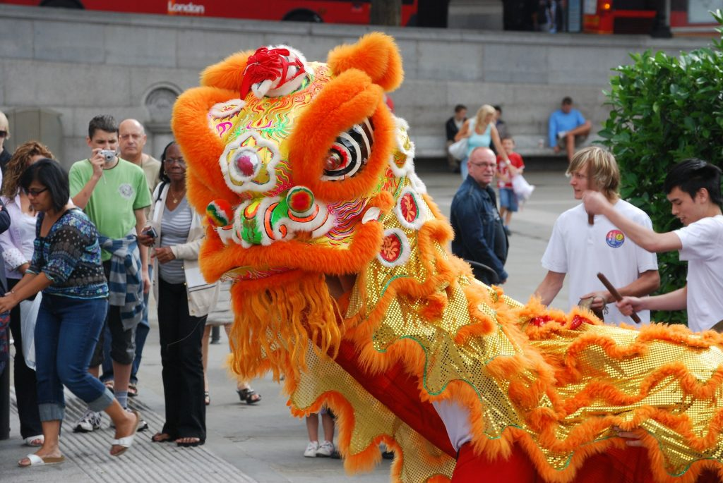 large costumed character offering a traditional dance at a Chinese New Year festival explore cultures