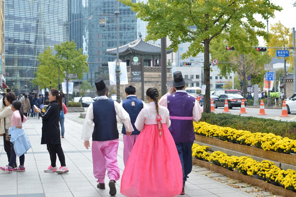 Photo of Koreans dressed in traditional clothing while walking down a street in the middle of a modern city