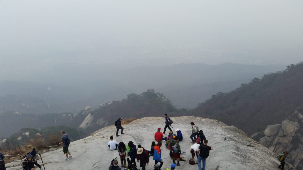 Photo of hikers at the top of a mountain looking out over the landscape