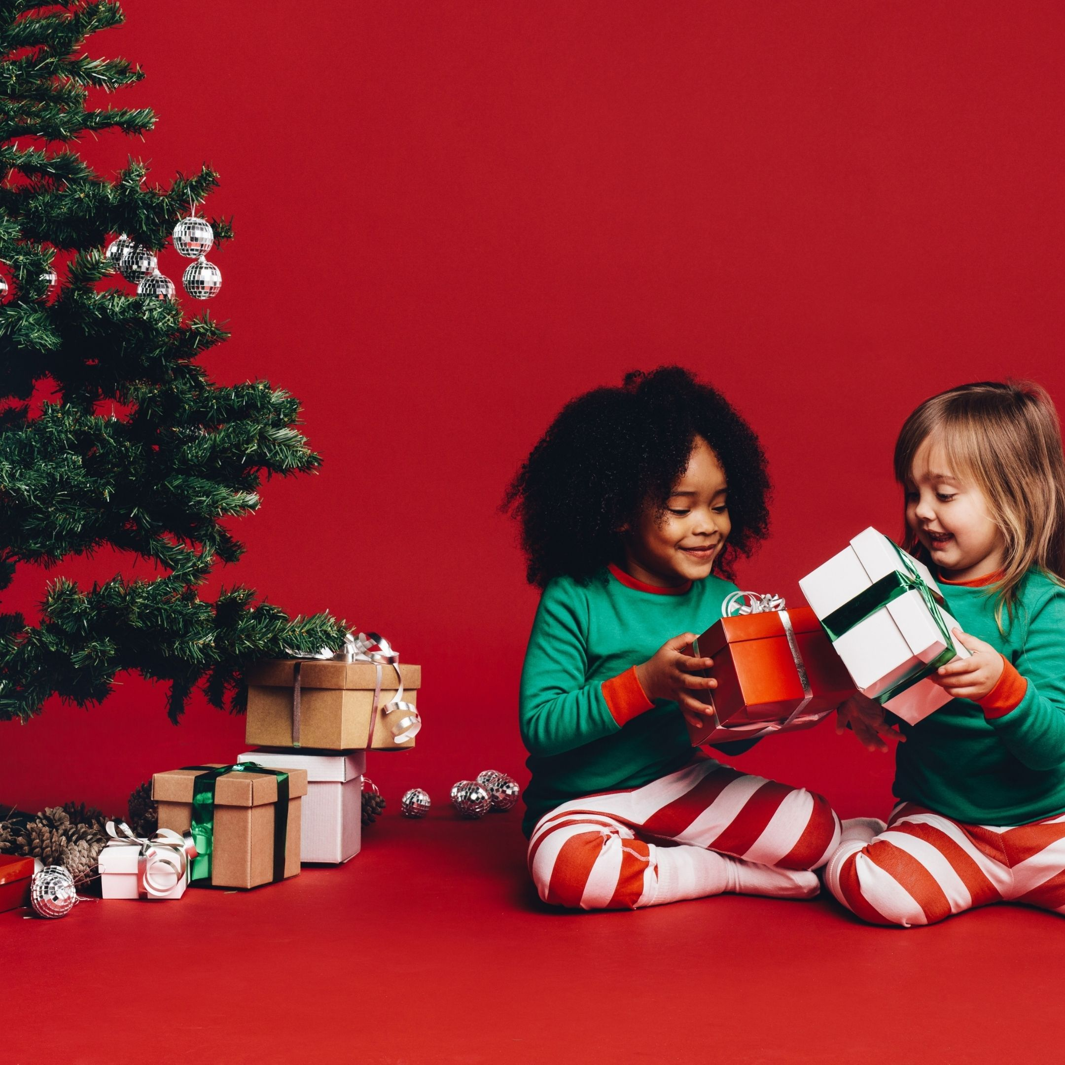 two girls sitting hear a Christmas tree getting ready to open their gifts gift ideas