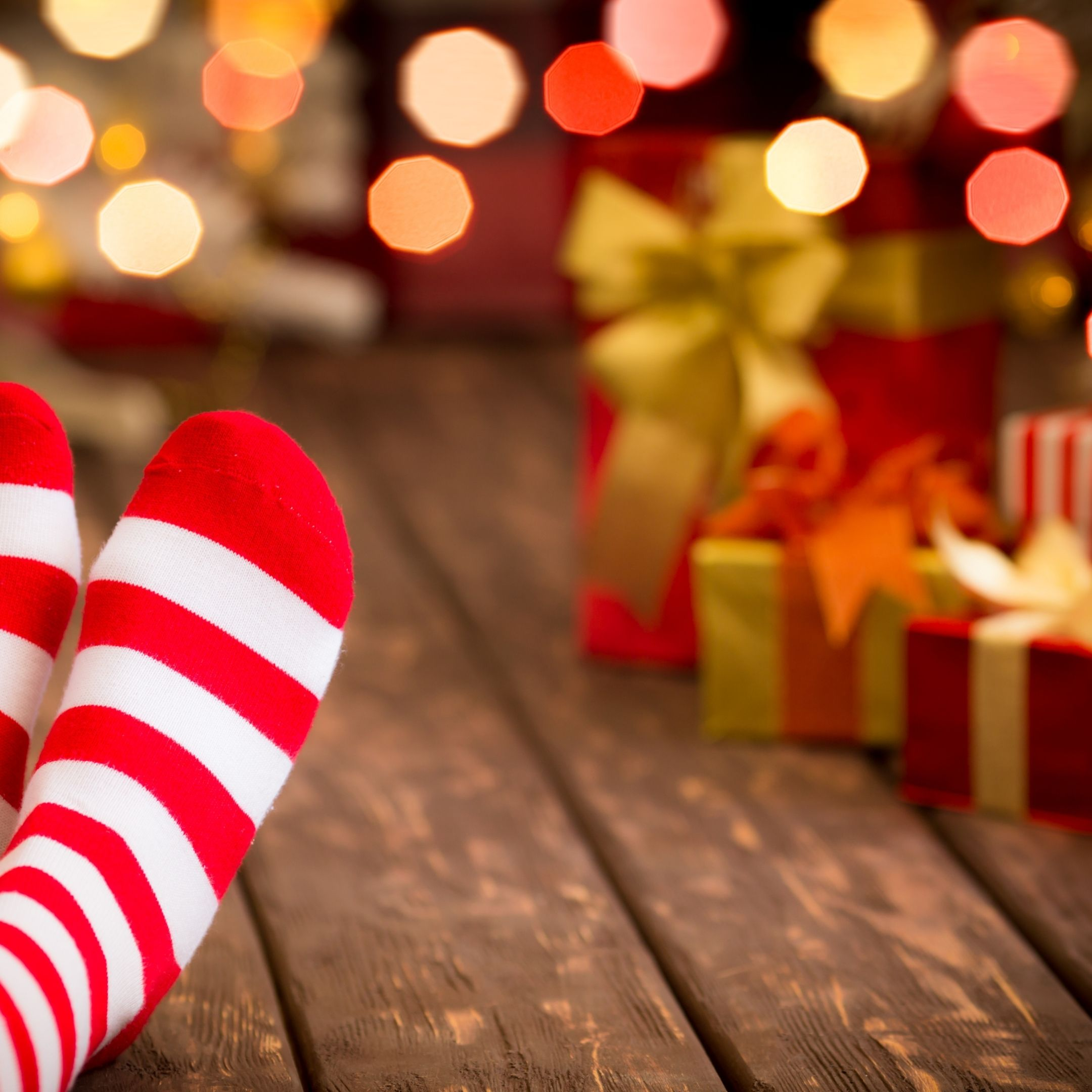 stocking feet near wrapped holiday gifts gift ideas