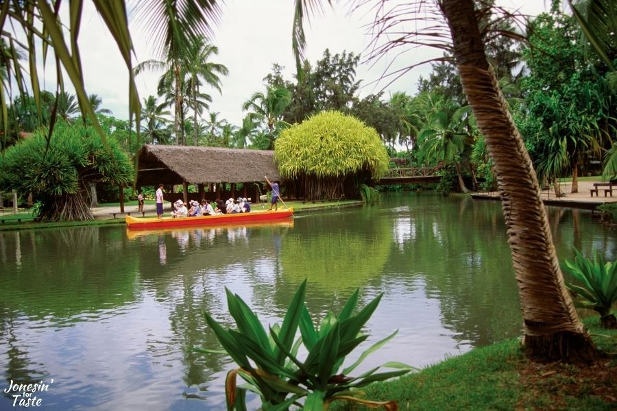 a flat top double hulled canoe full of people on the water in front of a thatched roof pavilion