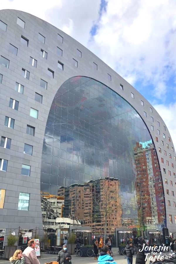 Looking up at the Markthal, a U shaped building with a large u shaped window that reflects the surrounding buildings