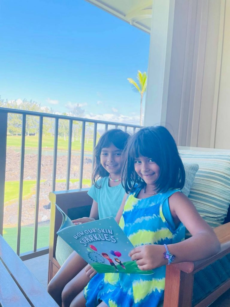 """The author's daughters reading the book """"How our Skin Sparkles"""" 