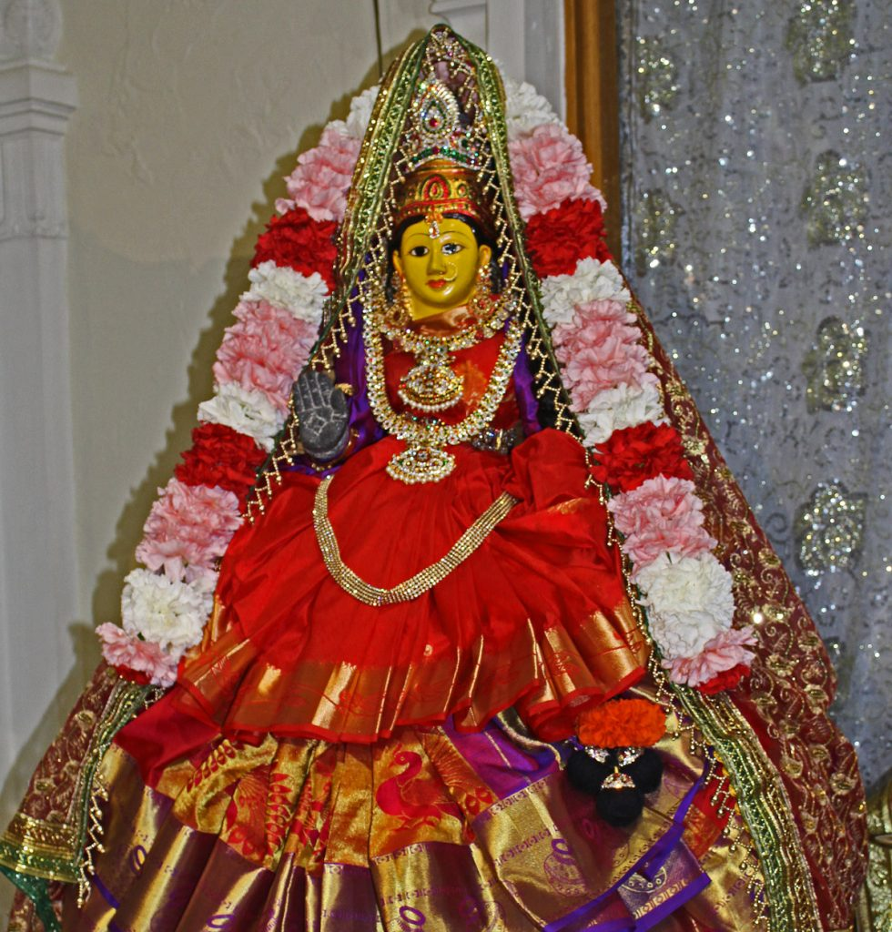 Lakshmi deity dressed in fine clothes and a flower lei